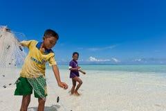 Enfants de poupées de mer pêchant un poisson Images libres de droits