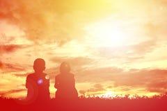 Enfants de silhouette sur le coucher du soleil Photographie stock libre de droits