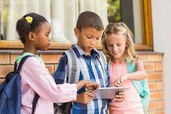 Enfants de sourire à l'aide d'a et de comprimé numérique Images stock
