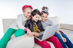Enfants de sourire à l'aide de l'ordinateur portable tout en se reposant sur le sofa Images stock