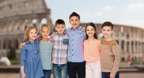 Enfants de sourire étreignant au-dessus du Colisé à Rome Image stock