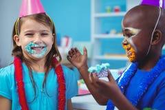 Enfants de sourire avec le glaçage sur leurs visages images stock