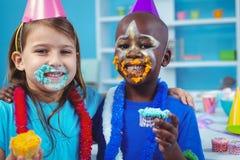 Enfants de sourire avec le glaçage sur leurs visages Photo libre de droits