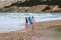 Enfants de sourire ayant l'amusement dans la plage Photographie stock