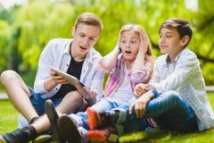 Enfants de sourire ayant l'amusement et le regard à marquer sur tablette à l'herbe Enfants jouant dehors en été les adolescents c Photographie stock