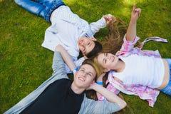 Enfants de sourire ayant l'amusement ou se trouvant dessus arrière et regardant le ciel Enfants jouant dehors en été Image libre de droits