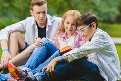 Enfants de sourire ayant le livre d'amusement et de lecture à l'herbe Enfants jouant dehors en été les adolescents communiquent e Images libres de droits