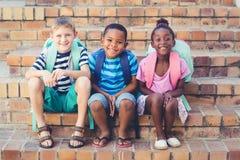 Enfants de sourire d'école se reposant ensemble sur des escaliers Photos stock