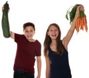 Enfants de sourire de consommation en bonne santé avec des carottes et le vegeta de courgette images libres de droits