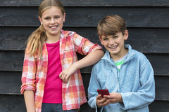 Enfants de sourire de garçon et de fille à l'aide du téléphone portable Image libre de droits