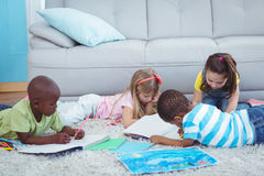 Enfants de sourire dessinant des photos sur le papier Image libre de droits