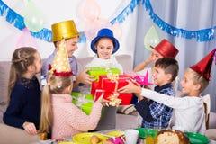 Enfants de sourire donnant des présents à la fille pendant la partie Photos libres de droits