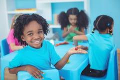 Enfants de sourire employant modelant l'argile Image stock