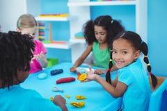 Enfants de sourire employant modelant l'argile Photos libres de droits