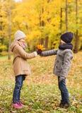 Enfants de sourire en parc d'automne Photographie stock libre de droits