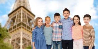 Enfants de sourire heureux étreignant au-dessus de Tour Eiffel Photo stock
