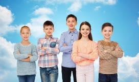 Enfants de sourire heureux au-dessus de ciel bleu Images stock