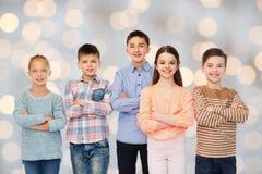 Enfants de sourire heureux au-dessus des lumières de vacances Photos stock