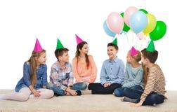 Enfants de sourire heureux dans des chapeaux de partie sur l'anniversaire Photos libres de droits