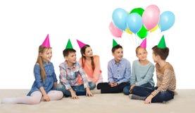 Enfants de sourire heureux dans des chapeaux de partie sur l'anniversaire Image libre de droits