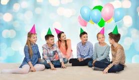 Enfants de sourire heureux dans des chapeaux de partie sur l'anniversaire Images stock