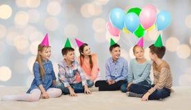 Enfants de sourire heureux dans des chapeaux de partie sur l'anniversaire Photo stock