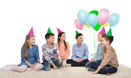 Enfants de sourire heureux dans des chapeaux de partie sur l'anniversaire Images libres de droits