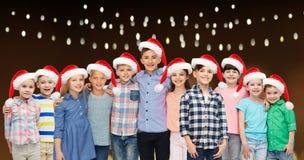 Enfants de sourire heureux dans des chapeaux de Santa de Noël Photos libres de droits