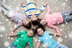 Enfants de sourire heureux se trouvant sur le plancher au-dessus de la neige Photographie stock