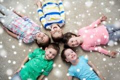 Enfants de sourire heureux se trouvant sur le plancher au-dessus de la neige Images libres de droits