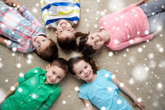 Enfants de sourire heureux se trouvant sur le plancher au-dessus de la neige Photos stock