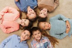 Enfants de sourire heureux se trouvant sur le plancher en cercle Photo libre de droits