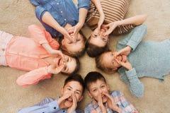 Enfants de sourire heureux se trouvant sur le plancher en cercle Photographie stock libre de droits