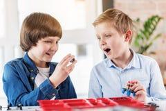 Enfants de sourire intéressés tenant des pièces de rechange Images stock