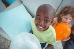 Enfants de sourire jouant avec des ballons photo stock
