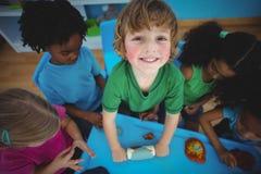 Enfants de sourire jouant avec modeler l'argile Photographie stock libre de droits