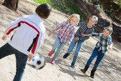 Enfants de sourire jouant le football de rue dehors Images stock