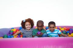 Enfants de sourire mignons dans la piscine de boule d'éponge Images stock