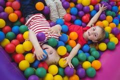 Enfants de sourire mignons dans la piscine de boule d'éponge Image stock