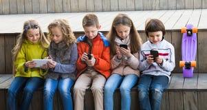 Enfants de sourire s'asseyant avec des périphériques mobiles Photographie stock