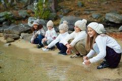 Enfants de sourire s'asseyant par l'eau Photo libre de droits