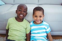 Enfants de sourire s'asseyant par le divan Images libres de droits