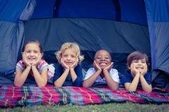 Enfants de sourire se situant dans la tente ensemble Images stock