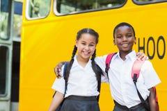 Enfants de sourire se tenant devant l'autobus scolaire Photos stock