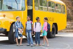 Enfants de sourire se tenant ensemble devant l'autobus scolaire Photographie stock