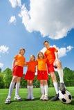 Enfants de taille différente avec le football dans la rangée Photographie stock