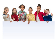 Enfants de teint différent tenant un blanc vide avec des pouces  Photo stock