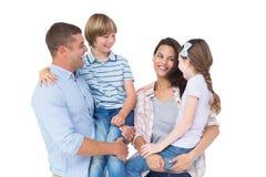 Enfants de transport de mère et de père au-dessus du fond blanc photographie stock