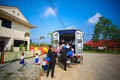 Enfants descendant de l'autobus scolaire par le professeur Image libre de droits