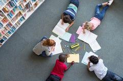 Enfants dessinant à la bibliothèque images libres de droits